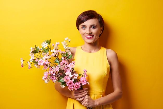 Portrait de femme tenant des fleurs roses
