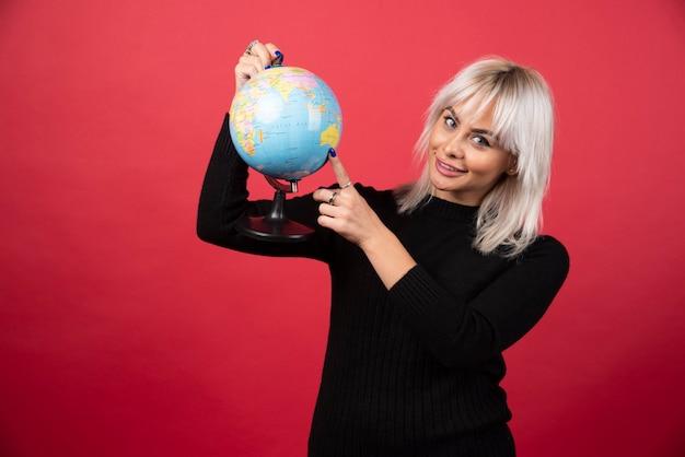 Portrait de femme tenant un globe terrestre sur un mur rouge.