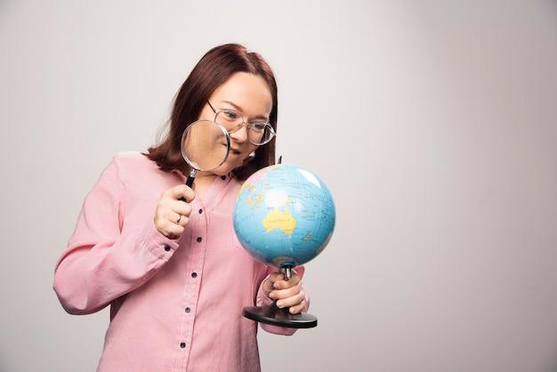 Portrait de femme tenant une loupe et un globe terrestre. photo de haute qualité