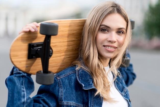 Portrait de femme tenant une planche à roulettes