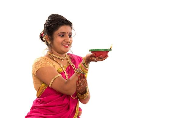 Portrait d'une femme traditionnelle indienne tenant diya, diwali ou deepavali photo avec des mains féminines tenant une lampe à huile pendant le festival de la lumière