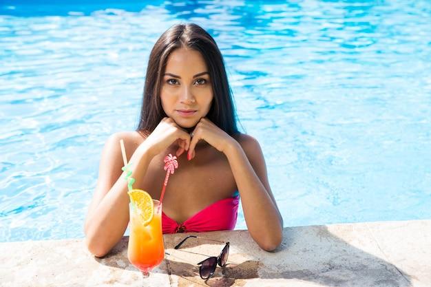 Portrait d'une femme en train de bronzer dans une piscine à l'extérieur