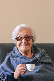 Portrait d'une femme très âgée buvant du café positif grand-mère de quatre-vingt-dix ans