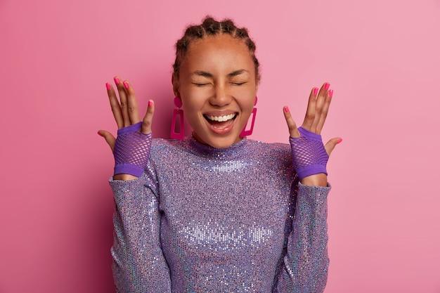 Portrait d'une femme très heureuse et amusée a la peau foncée, lève les mains, montre des gants de sport, porte un pull violet scintillant, rit positivement, entend quelque chose d'hilarant, des modèles sur un mur rose pastel