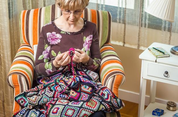 Portrait de femme tricotant une courtepointe en laine vintage
