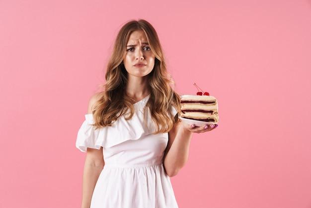 Portrait de femme triste caucasienne vêtue d'une robe blanche regardant devant et tenant un morceau de gâteau isolé sur un mur rose