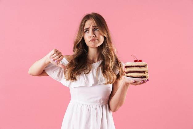 Portrait d'une femme triste déçue vêtue d'une robe blanche tenant un morceau de gâteau avec le pouce vers le bas isolé sur un mur rose