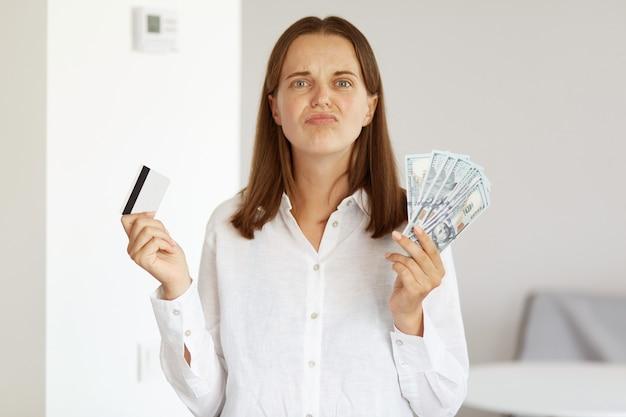 Portrait d'une femme triste et insatisfaite portant une chemise blanche de style décontracté, posant dans une pièce lumineuse à la maison, tenant une carte de crédit et un grand fan d'argent, regardant la caméra avec une expression bouleversée.
