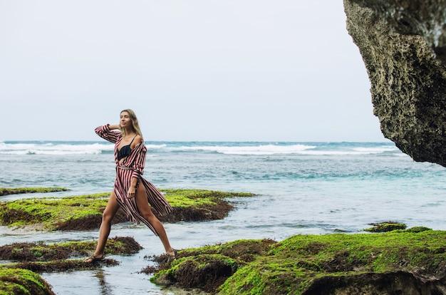 Portrait de femme en tunique et bikini sur une belle plage de récif parmi les rochers sensuels et émotionnels