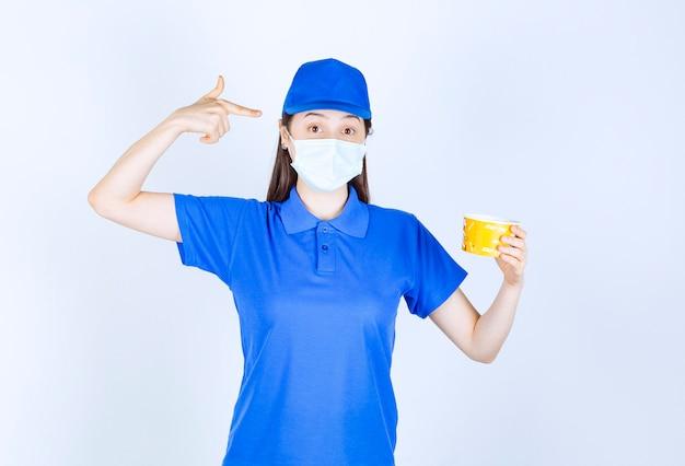 Portrait de femme en uniforme et masque médical pointant sur une tasse en plastique