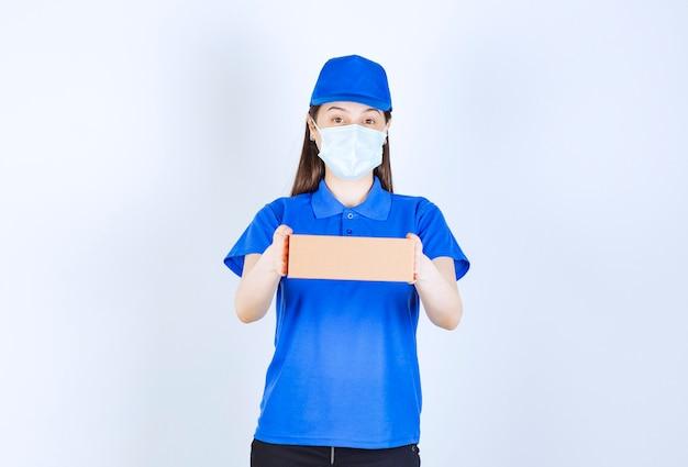 Portrait de femme en uniforme et masque médical tenant une boîte en papier