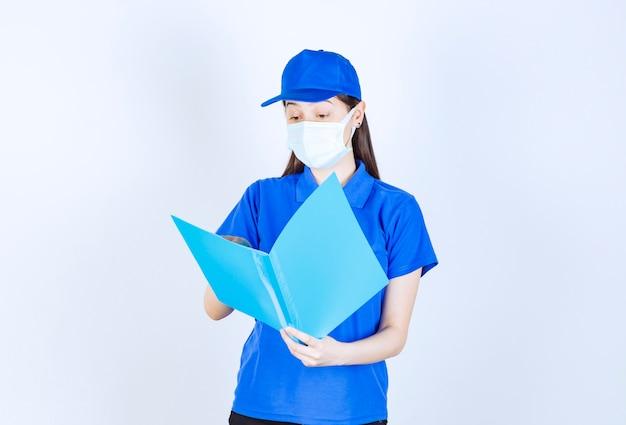 Portrait de femme en uniforme et masque médical tenant le dossier