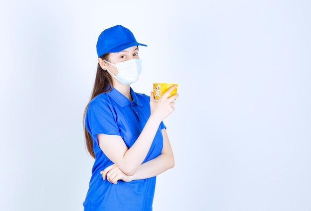Portrait de femme en uniforme et masque médical tenant une tasse en plastique