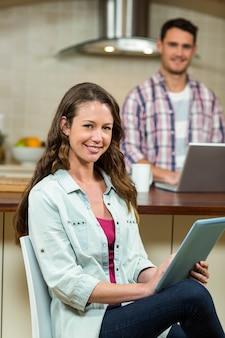 Portrait, femme, utilisation, tablette numérique, dans, cuisine, tandis que, homme, utilisation, ordinateur portable, dans, fond