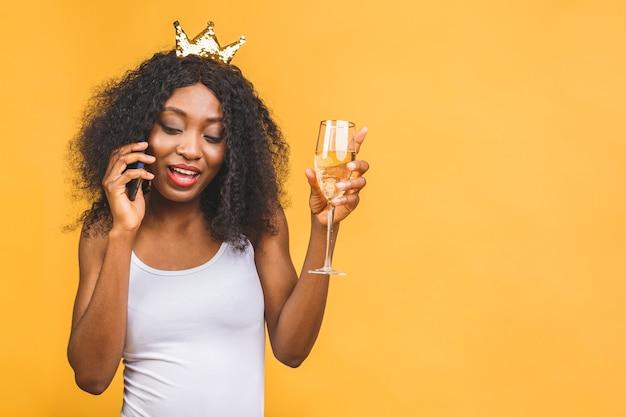 Portrait de femme avec verre de champagne et couronne d'or, parler au téléphone