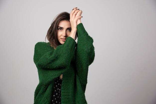 Portrait de femme en veste verte debout sur gris.