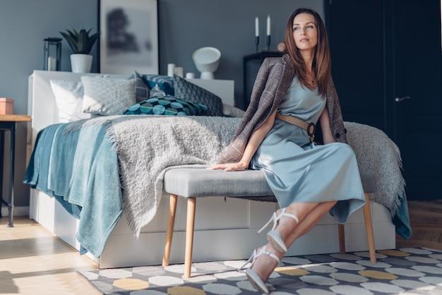 Portrait de femme vêtue d'une robe à la maison dans la chambre assise sur une banquette de chevet.