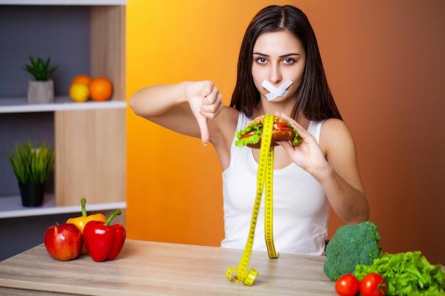 Portrait femme veut manger un hamburger mais coincé la bouche skochem, le concept de régime.