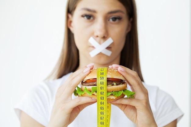 Portrait femme veut manger un hamburger mais coincé bouche skochem