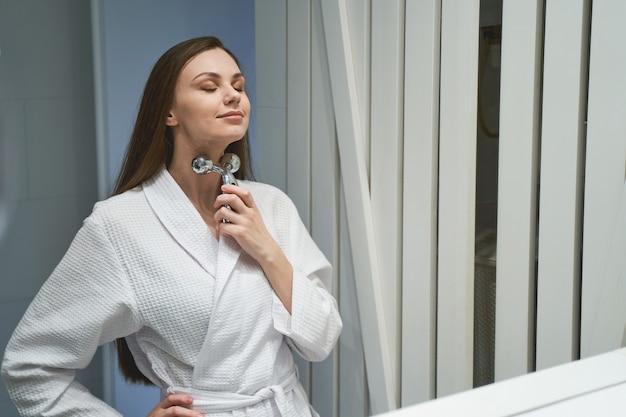 Portrait d'une femme les yeux fermés en massant son cou avec un rouleau de massage en forme de y