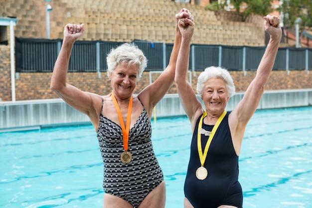 Portrait de femmes âgées excitées avec des médailles d'or debout au bord de la piscine