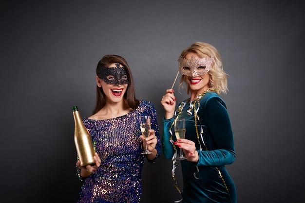 Portrait de femmes en masques buvant du champagne