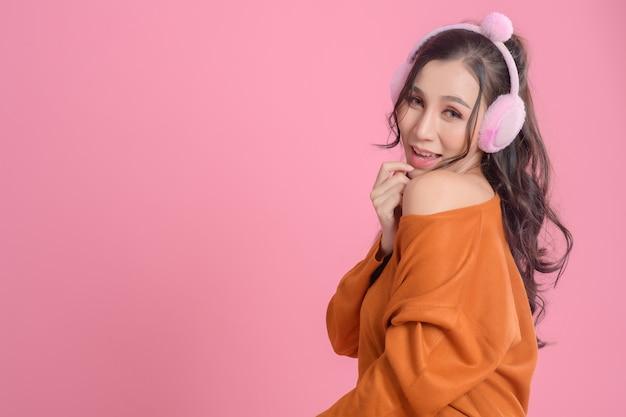 Portrait de femmes mignonnes avec des écouteurs portant un pull orange sur rose