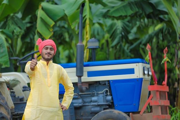 Portrait de fermier indien avec tracteur et montrant des coups vers le haut