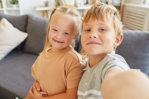 Portrait de fier frère prenant selfie avec jolie fille trisomique alors qu'il était assis sur un canapé à la maison ensemble, copiez l'espace