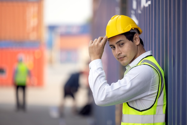 Portrait de fier ingénieur en vêtements de travail de protection debout dans une cour d'expédition