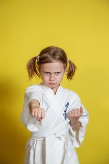 Portrait de fille de 5 ans en kimono pratiquer le karaté contre surface jaune à la maison