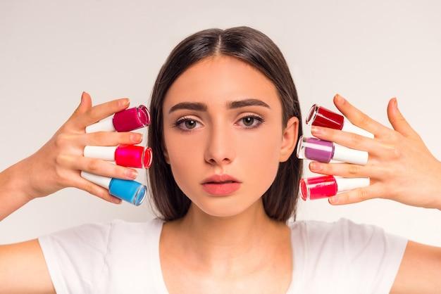 Portrait d'une fille adolescente joyeuse est titulaire de vernis à ongles au doigt.