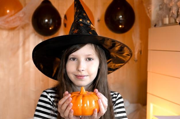 Portrait d'une fille adorable portant un chapeau d'halloween tenant une citrouille et une fête d'halloween souriante