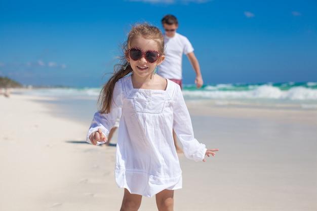 Portrait d'une fille adorable et son père avec sa petite soeur sur une plage tropicale