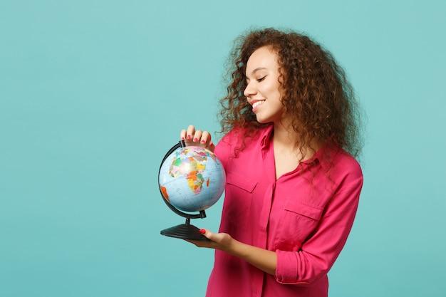 Portrait d'une fille africaine curieuse dans des vêtements décontractés tenant dans les mains un globe terrestre isolé sur fond bleu turquoise en studio. les gens émotions sincères, concept de style de vie. maquette de l'espace de copie.