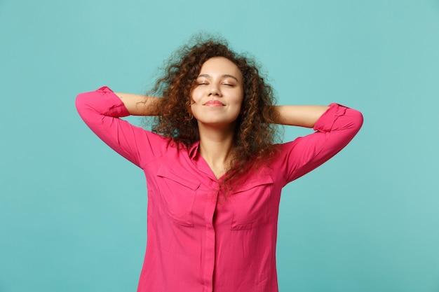 Portrait d'une fille africaine détendue dans des vêtements décontractés en gardant les yeux fermés, mettant les mains derrière la tête isolée sur fond bleu turquoise. les gens émotions sincères, concept de style de vie. maquette de l'espace de copie.