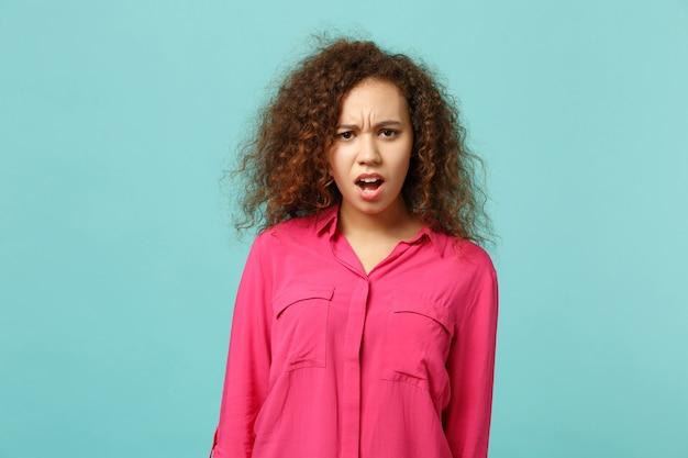 Portrait d'une fille africaine irritée et perplexe dans des vêtements décontractés à la recherche d'un appareil photo, jurant isolé sur fond bleu turquoise en studio. concept de mode de vie des émotions sincères des gens. maquette de l'espace de copie.