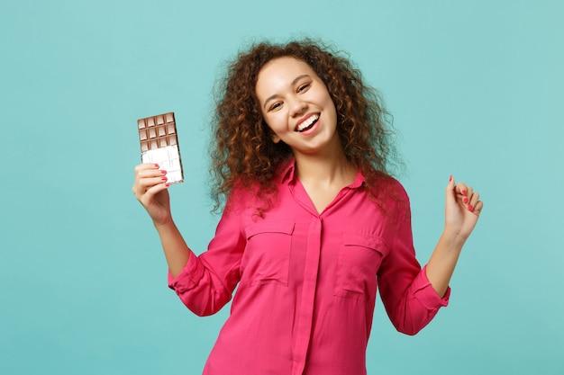 Portrait d'une fille africaine joyeuse dans des vêtements décontractés tenant à la main une barre de chocolat isolée sur fond de mur bleu turquoise en studio. les gens émotions sincères, concept de style de vie. maquette de l'espace de copie.