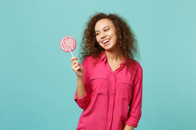 Portrait d'une fille africaine joyeuse dans des vêtements décontractés tenant à la main une sucette ronde rose isolée sur fond bleu turquoise en studio. les gens émotions sincères, concept de style de vie. maquette de l'espace de copie.