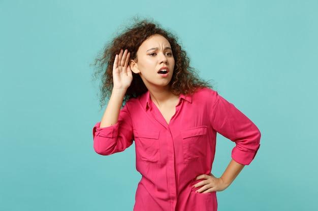 Portrait d'une fille africaine perplexe dans des vêtements décontractés espionnant avec un geste auditif isolé sur fond de mur bleu turquoise en studio. concept de mode de vie des émotions sincères des gens. maquette de l'espace de copie.