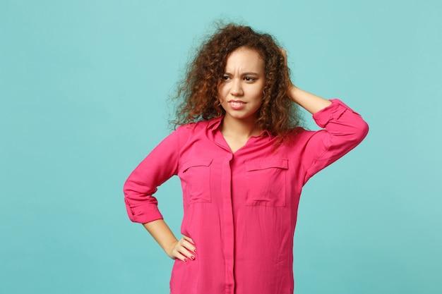 Portrait d'une fille africaine préoccupée dans des vêtements décontractés regardant de côté, mettant la main sur la tête isolée sur fond de mur bleu turquoise. concept de mode de vie des émotions sincères des gens. maquette de l'espace de copie.