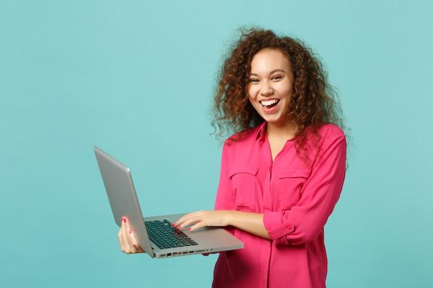 Portrait d'une fille africaine qui rit dans des vêtements décontractés roses à l'aide d'un ordinateur portable isolé sur fond de mur bleu turquoise en studio. les gens émotions sincères, concept de style de vie. maquette de l'espace de copie.