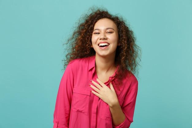 Portrait d'une fille africaine qui rit dans des vêtements décontractés roses tenant la main sur la poitrine isolée sur fond de mur bleu turquoise en studio. les gens émotions sincères, concept de style de vie. maquette de l'espace de copie.