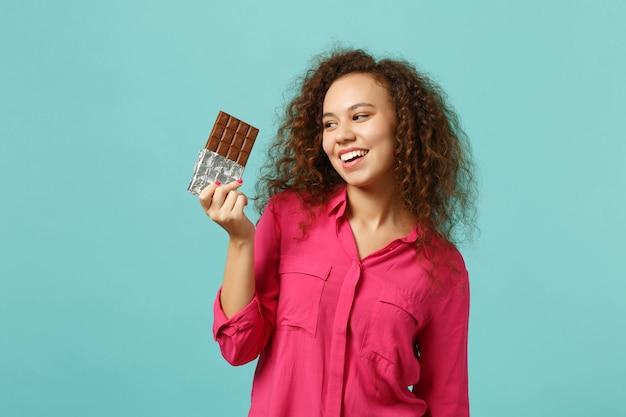 Portrait d'une fille africaine qui rit dans des vêtements décontractés tenant à la main une barre de chocolat isolée sur fond de mur bleu turquoise en studio. les gens émotions sincères, concept de style de vie. maquette de l'espace de copie.