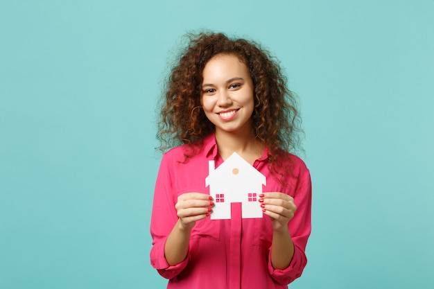 Portrait d'une fille africaine souriante dans des vêtements décontractés roses tenant dans une maison de papier à la main isolée sur fond de mur bleu turquoise en studio. concept de mode de vie des émotions sincères des gens. maquette de l'espace de copie.