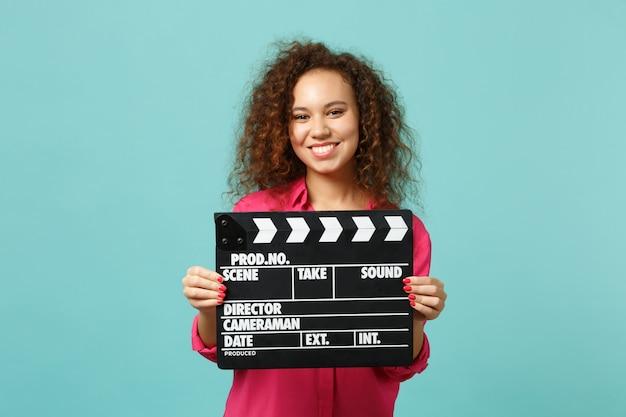 Portrait d'une fille africaine souriante dans des vêtements décontractés tenant un film noir classique faisant un clap isolé sur fond bleu turquoise. les gens émotions sincères, concept de style de vie. maquette de l'espace de copie.