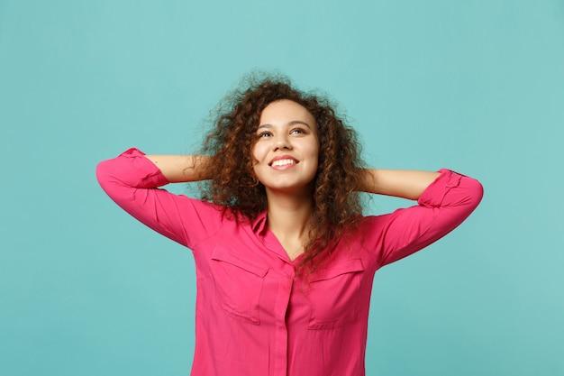 Portrait d'une fille africaine souriante pensive dans des vêtements décontractés en levant, mettant les mains derrière la tête isolée sur fond bleu turquoise. les gens émotions sincères, concept de style de vie. maquette de l'espace de copie.