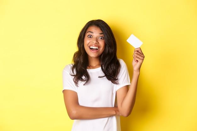 Portrait d'une fille afro-américaine étonnée soulevant une carte de crédit et souriante excitée de faire du shopping