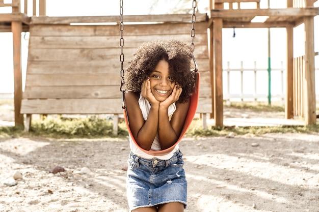 Portrait d'une fille afro-américaine souriante regarde le concept d'enfance et de bonheur de la caméra
