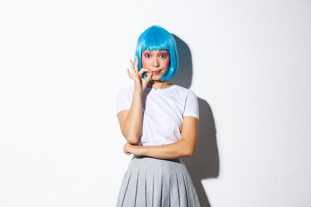 Portrait de fille asiatique coquette en perruque bleue scelle ses lèvres et promet de ne pas dire de secret, debout.